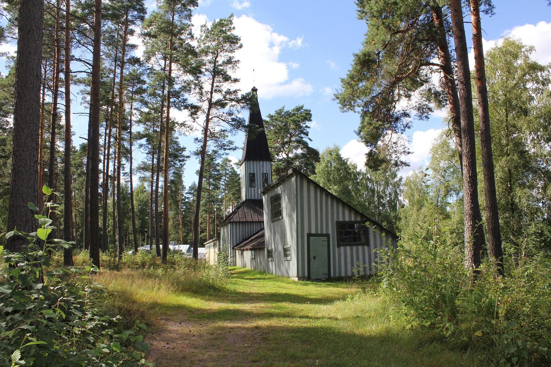 pieni harmaa kirkko metsässä