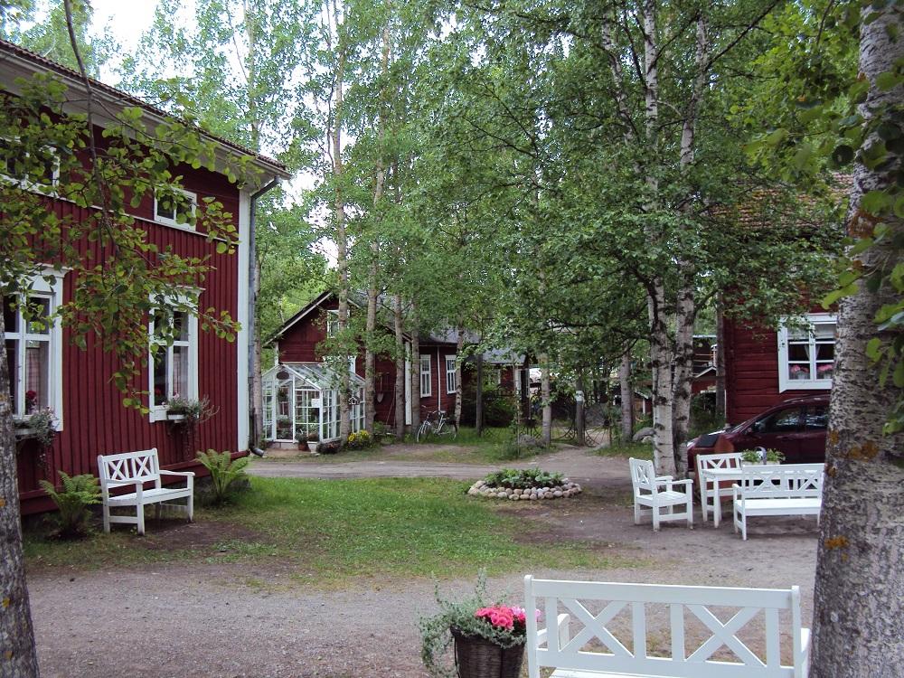 Vanha pihapiiri. Punamultamaalattuja taloja ja valkoisia puistonpenkkejä. Koivuja ja muita lehtipuita.