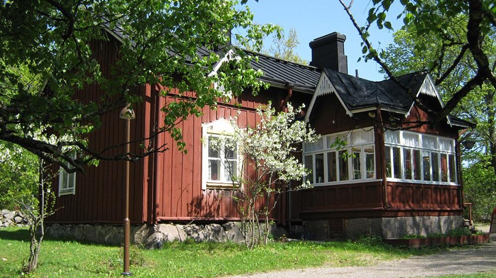 vanha punamultamaalattu talo, valkoiset ikkunanpuitteet, kuvattu alkukesällä, ikkunan edessä pieni kukkiva puu