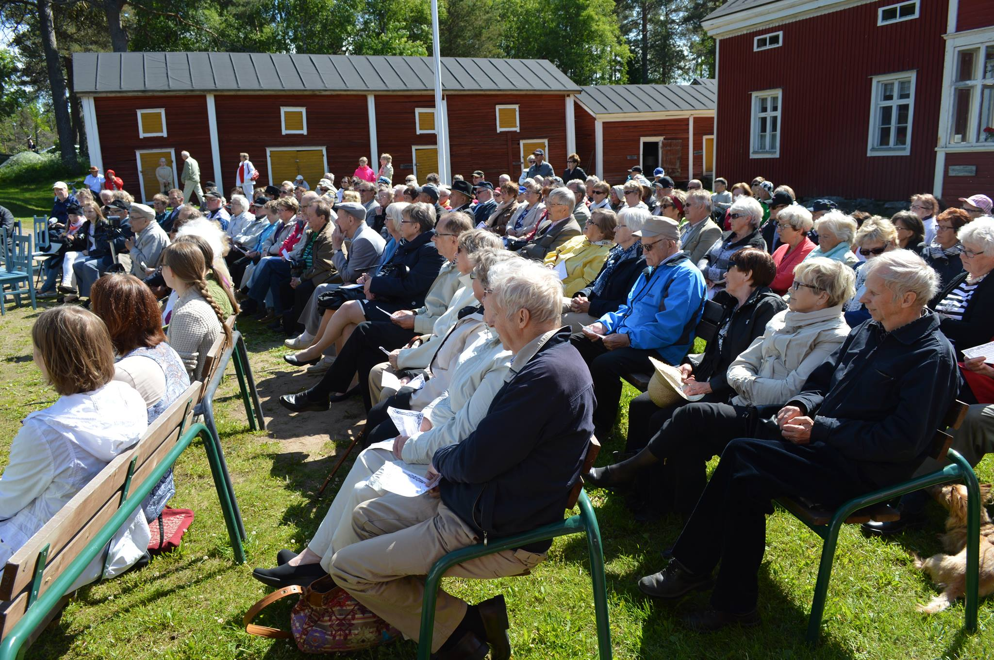 Ihmisiä istumassa penkeillä nurmikolla vanhan talon pihapiirissä kesällä