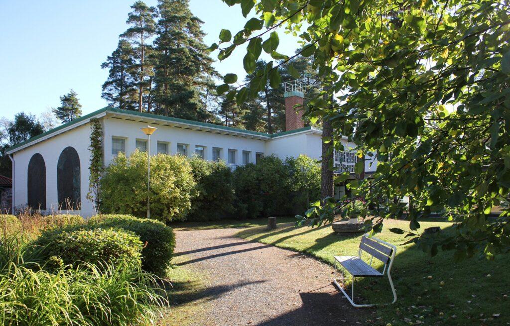 valkoinen moderni museorakennus puistomaisemassa. etualalla puistonpenkki. Pihaköytävä, nurmikoa, pensaita, istutuksia ja perennoja